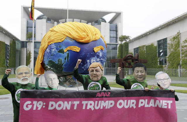 <p>Demonstrators protest on June 29 against the climate policy of President Trump as they wear masks of Indian Prime Minister Narendra Modi, French President Emmanuel Macron, German Chancellor Angela Merkel, Chinese President Xi Jinping and European Commission President Jean-Claude Juncker, from left, prior to a gathering of European leaders on the G-20 summit in the chancellery in Berlin. (Photo: Michael Sohn/AP) </p>