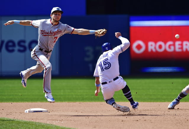 Toronto Blue Jays' Randal Grichuk (15) steals second base as the Washington Nationals shortstop Trea Turner (7) cannot catch the throw during seventh-inning baseball game action in Toronto, Sunday, June 17, 2018. (Frank Gunn/The Canadian Press via AP)