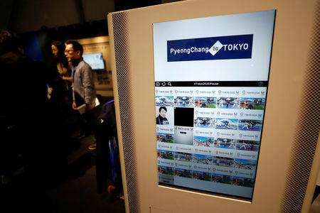 People stand next to a machine which prints photographs of the visitors during the Tokyo 2020 Japan House media preview in Gangneung, South Korea, February 8, 2018. REUTERS/Jorge Silva