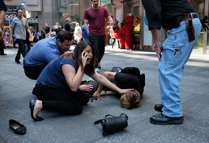 <p>MAY 18, 2017 – People attend to an injured man after a car plunged into him in Times Square in New York.<br> A car plowed into a crowd of pedestrians in New York's bustling Times Square, leaving one person dead and at least 12 other injured. (Photo: Jewel Samad/AFP/Getty Images) </p>