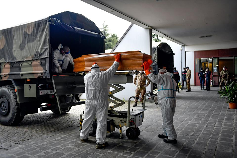 coronovirus bergamo italy workers loading coffins caskets military trucks march 2020 AP_20087465378485