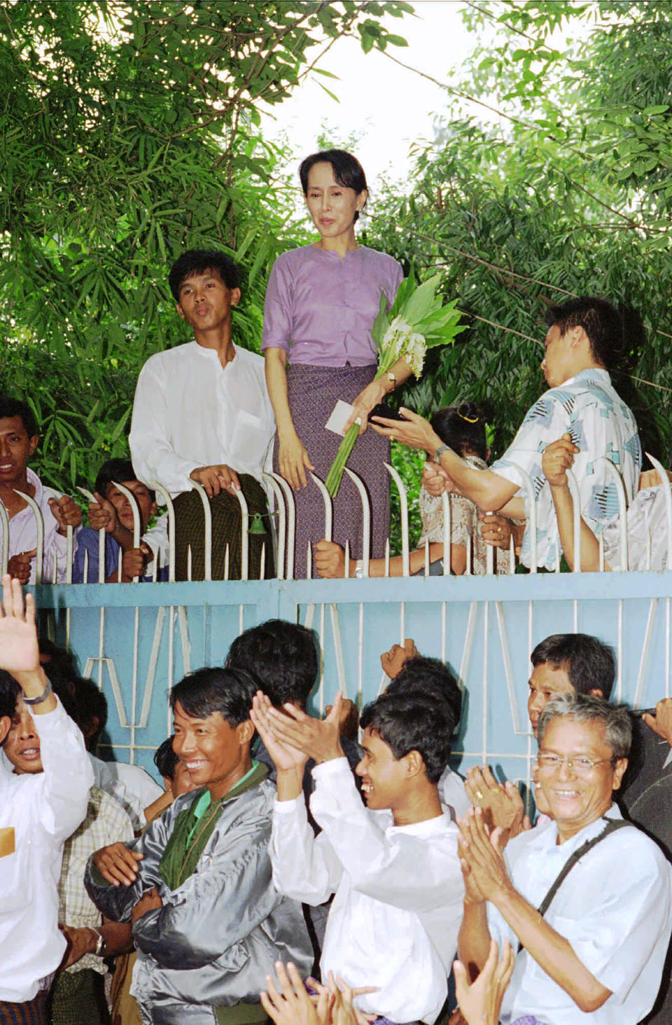 In this July 11, 1995, file photo, pro-democracy leader Aung San Suu Kyi stands behind her gate to greet a crowd of some 1,000 people who have come to see her after her release from house arrest in Yangon, Myanmar. After Myanmar's military staged a coup Monday, Feb. 1, 2021, Aung San Suu Kyi finds herself back under house arrest. But this time, her standoff with the generals comes after she has sorely disappointed many once-staunch supporters in the international community. (AP Photo/Stuart Isett, File)