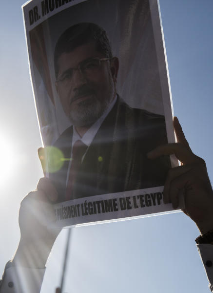 A man holds a picture of ousted former Egyptian President Mohammed Morsi in Tunis, Tunisia. Tuesday, June 18, 2019. The former president, who was ousted by current President Abdel-Fattah el-Sissi in a military coup in 2013, collapsed in a courtroom in Egypt during trial on Monday and died. (AP Photo/Hassene Dridi)