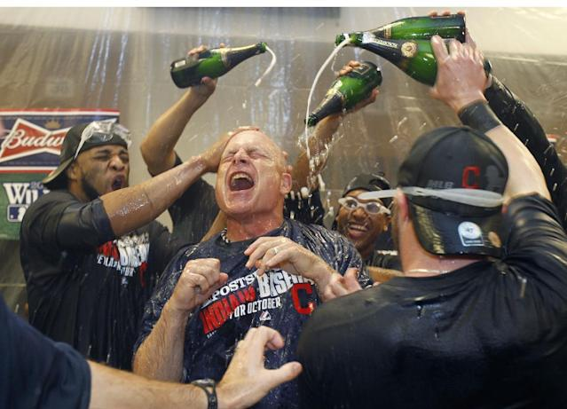 Cleveland Indians third base coach Brad Mills, center, is showered with champagne in the locker room after the Indians beat the Twins 5-1 in a baseball game in Minneapolis, Sunday, Sept. 29, 2013, to clinch a wild card spot in the playoffs. (AP Photo/Ann Heisenfelt)