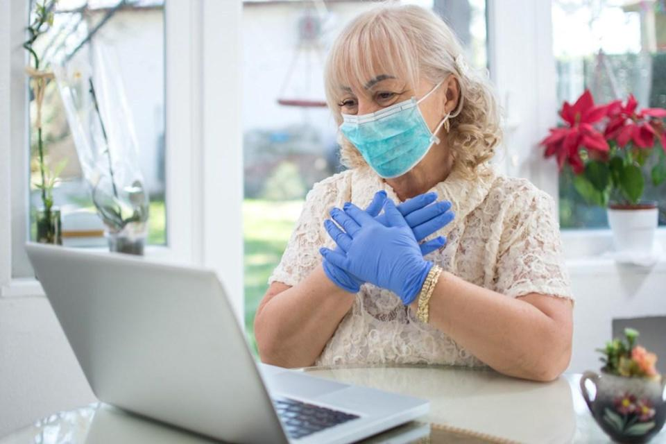 Scared mid age woman wearing protective mask and gloves reading news on laptop at home
