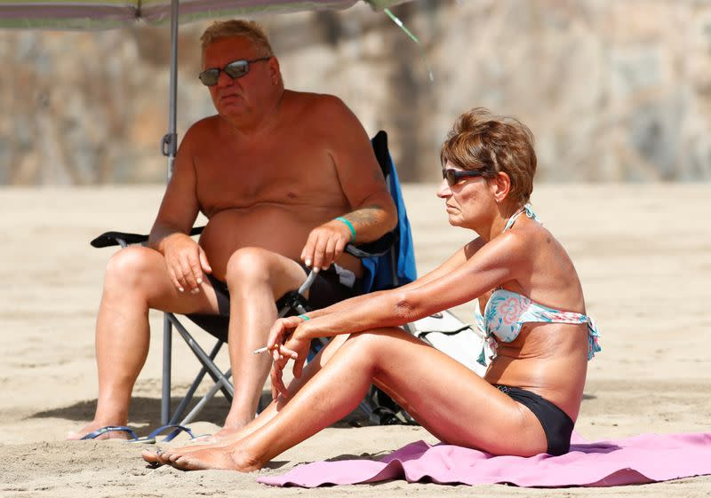 FILE PHOTO: A woman smokes a cigarette while sunbathing on the beach, as the regional government of the Canary Islands forbids smoking without maintaining a safe distance
