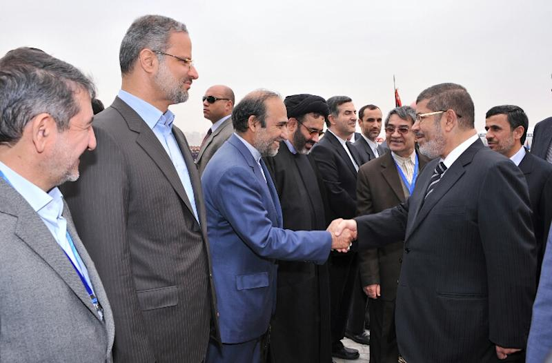 In this image released by the Egyptian Presidency, Iran's President Mahmoud Ahmadinejad, right, looks on as and Egyptian President Mohammed Morsi, second right, shakes hands with the Iranian delegation at the airport in Cairo, Egypt, Tuesday, Feb. 5, 2013. Ahmadinejad arrived in Cairo on Tuesday for the first visit by an Iranian leader in more than three decades, marking a historic departure from years of frigid ties between the two regional heavyweights.(AP Photo/Egyptian Presidency)