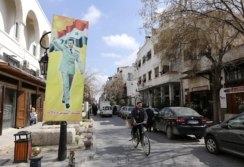 A Syrian man rides a bike past a banner bearing a picture of Syrian President Bashar al-Assad in the city of Damascus on March 5, 2015 (AFP Photo/Louai Beshara)