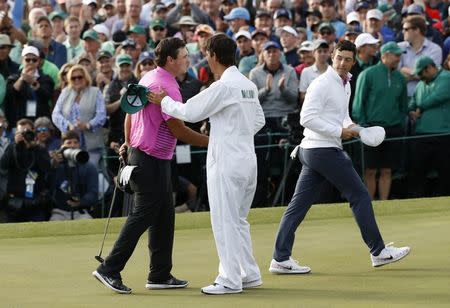 Patrick Reed of the U.S. (L) is congratulated by his caddie Kessler Karain as he celebrates winning the 2018 Masters tournament while Rory McIlroy of Northern Ireland (R) walks off the green after final round play at the Augusta National Golf Club in Augusta, Georgia, U.S. April 8, 2018. REUTERS/Mike Segar