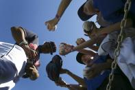 Cleveland Indians' Francisco Lindor, left, signs autographs for fans, signing gloves, baseballs, hats and uniforms prior to the team's spring training baseball game against the Chicago Cubs on Saturday, March 7, 2020, in Goodyear, Ariz. Lindor and many Indians players signed autographs for fans Saturday, even as the MLB set new policies in place as a precaution due to the coronavirus. (AP Photo/Ross D. Franklin)
