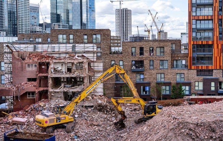 A digger on an urban construction site featuring new homes and high-rise buildings