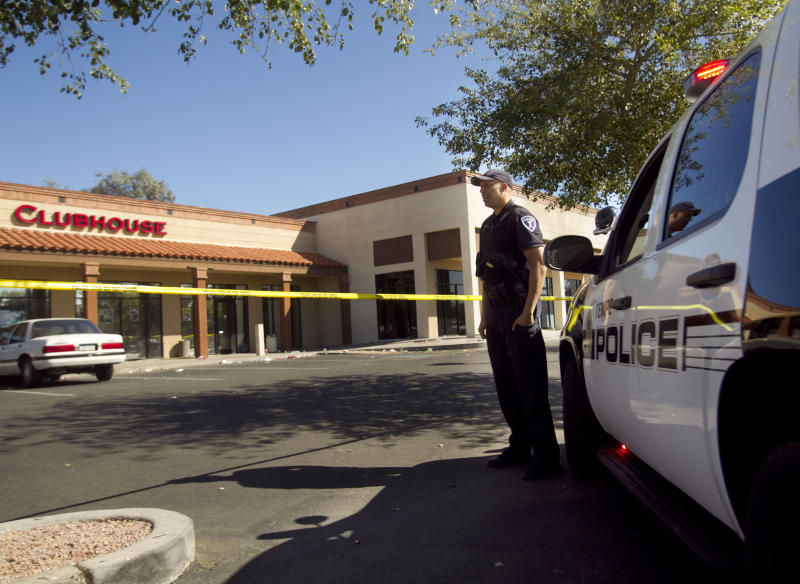 Tempe police officer T. Williams secures  the scene at the Clubhouse Music Venue, Saturday, March 3, 2012 in Tempe, Ariz. Police in the Phoenix suburb of Tempe say they've made one arrest and are looking for two other suspects after a shooting outside a nightclub left more than a dozen people wounded. (AP Photo/The Arizona Republic, David Wallace)  MARICOPA COUNTY OUT; MAGS OUT; NO SALES