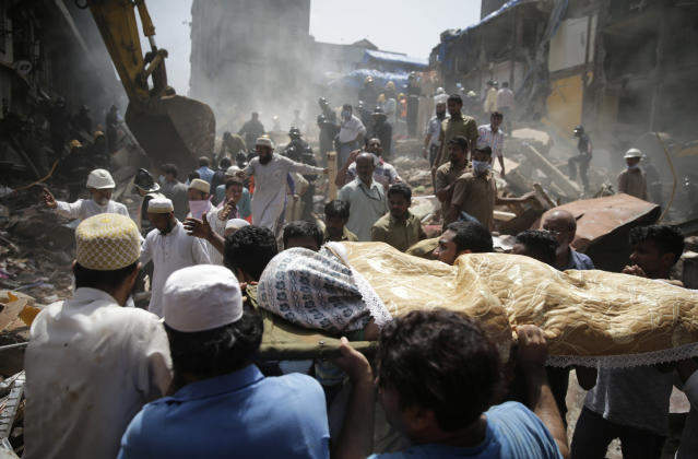 <p>The body of a victim is carried out from the site of a building collapse in Mumbai, India, Aug. 31, 2017. (Photo: Rafiq Maqbool/AP) </p>