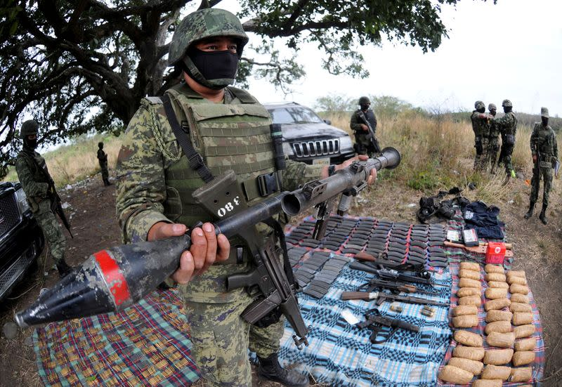 FILE PHOTO: A soldier holds up a seized grenade launcher after an operation at the village of Guayabal