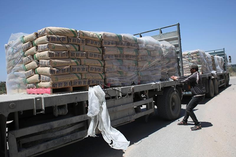 A Palestinian removes bags of cement from a truck which entered the southern Gaza Strip from Israel in 2015