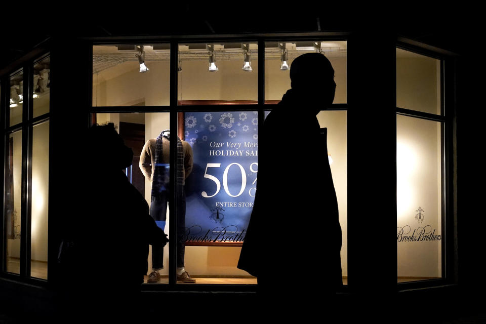 FILE - In this Saturday, Dec. 19, 2020 file photo, people walk past the window display of a store in Skokie, Ill. A closely-watched gauge for U.S. consumer confidence released on Tuesday, Dec. 22, 2020, tumbled to a reading of 88.6 in December as rising coronavirus cases tamped down American optimism to its lowest level since summer. (AP Photo/Nam Y. Huh)