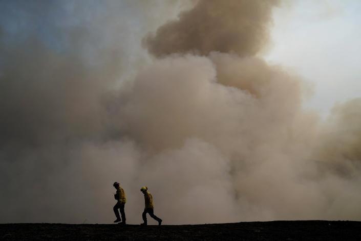 Two firefighters walk along the ridge as smoke from the Blue Ridge Fire rises Tuesday, Oct. 27, 2020, in Yorba Linda, Calif. Crews tried to beat back two out-of-control wildfires in Southern California on Tuesday that have kept tens of thousands of people out of their homes even as another round of dangerous fire weather raises the risk for flames erupting across the state. (AP Photo/Jae C. Hong)
