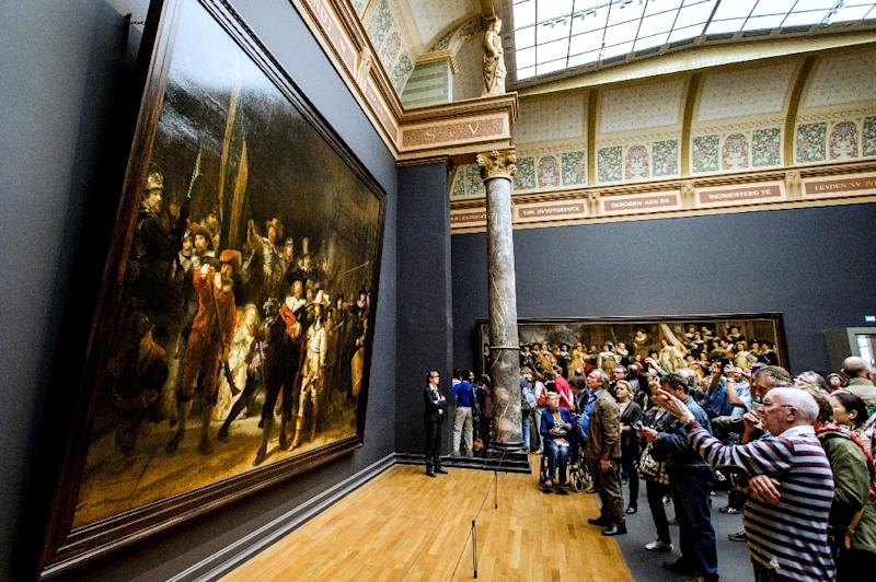"""Visitors looks at Rembrandt's """"The Night Watch"""" in the Rijksmuseum in Amsterdam, on May 17, 2015 (AFP Photo/Robin van Lonkhuijsen)"""