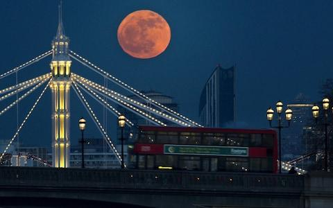 The full moon appears red above London's Albert bridge and Battersea Bridge in 2012 - Credit: Anthony Devlin