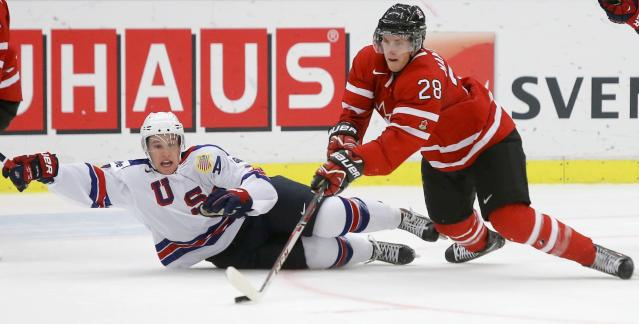 Canada's Anthony Mantha (R) and United States' Matt Grzelcyk battle for the puck during the second period of their IIHF World Junior Championship ice hockey game in Malmo, Sweden, December 31, 2013. REUTERS/Alexander Demianchuk (SWEDEN - Tags: SPORT ICE HOCKEY)