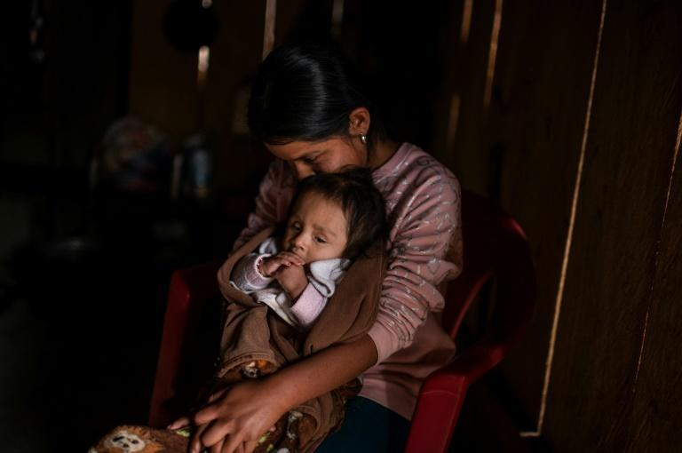 A Mexican mother holds her baby at her home in Metlatonoc in Guerrero state, where calls are growing for an end to the ancestral tradition of selling daughters into marriage