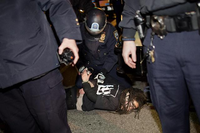 "Police officers arrest a demonstrator during after a vigil held for Kimani ""Kiki"" Gray in the East Flatbush neighborhood of New York's Brooklyn borough, Wednesday, March 13, 2013, in New York. According to the NYPD, the teen pointed a .38-caliber revolver at the plainclothes officers, who responded by shooting him to death. (AP Photo/John Minchillo)"