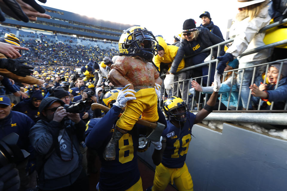 Michigan linebacker Devin Gil (8) carries the Paul Bunyan Trophy after beating Michigan State 44-10 in an NCAA college football game in Ann Arbor, Mich., Saturday, Nov. 16, 2019. (AP Photo/Paul Sancya)