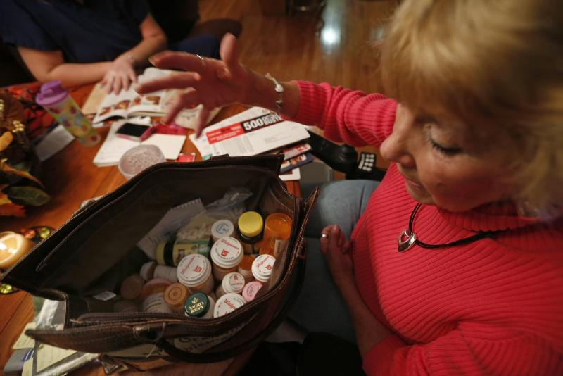 Wright looks over her list of medications at her home in Peoria, Illinois