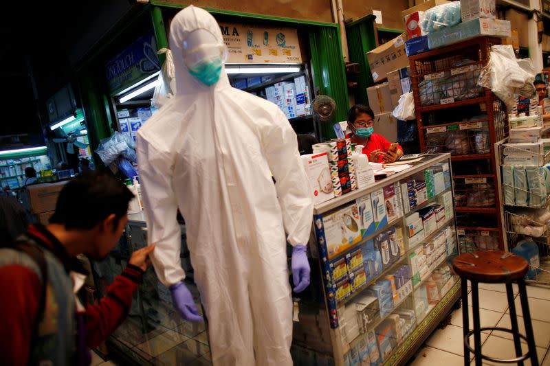 FILE PHOTO: A vendor wearing a mask waits for customers while a man looks at a protective suit displayed for sale at whole-sale market for medical stuffs, following the outbreak of the new coronavirus in China, in Jakarta