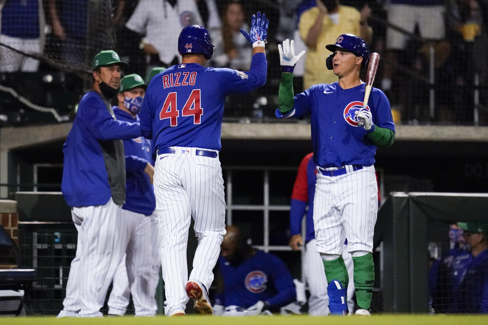 Chicago Cubs' Anthony Rizzo (44) high-fives Joc Pederson, right, after hitting a home run during the fourth inning of a spring training baseball game against the San Diego Padres Wednesday, March 17, 2021, in Mesa, Ariz. (AP Photo/Ashley Landis)