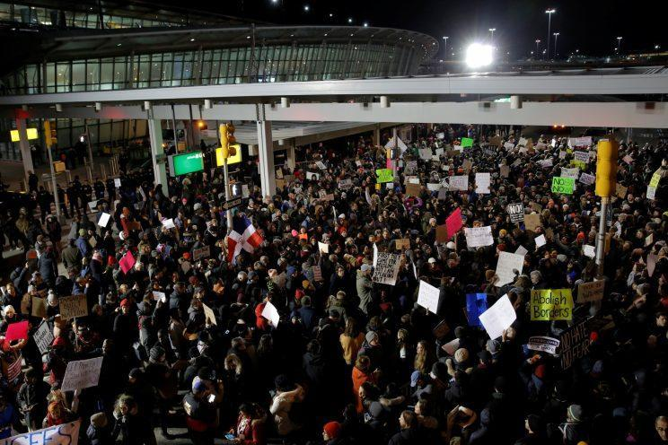 People participate in a protest against Trump's travel ban outside Terminal 4 at John F. Kennedy International Airport in New York City on Saturday night. (Andrew Kelly/Reuters)