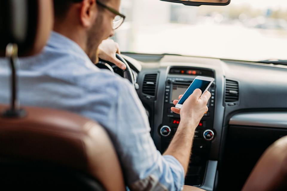 Man looking at mobile phone while driving a car. (Photo: nd3000 via Getty Images)
