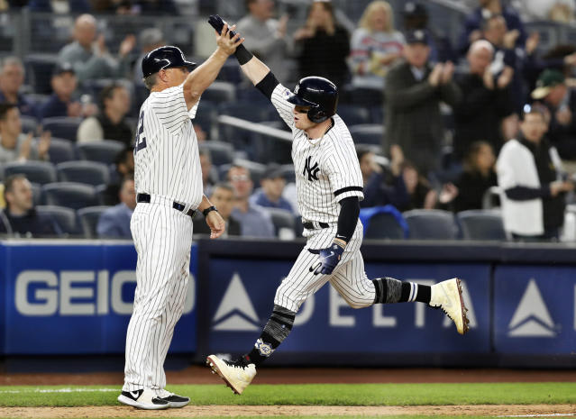 New York Yankees' Clint Frazier, right, trades high-fives with third base coach Phil Nevin after hitting a solo home run off Boston Red Sox starting pitcher Chris Sale during the fourth inning of a baseball game Tuesday, April 16, 2019, in New York. (AP Photo/Kathy Willens)
