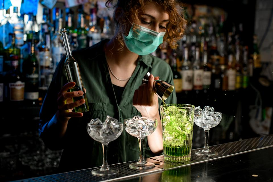Young bartender girl in a medical mask pour green liquid from beaker into glass with ice. Medical mask for prophylaxis and protection from coronavirus COVID-19.