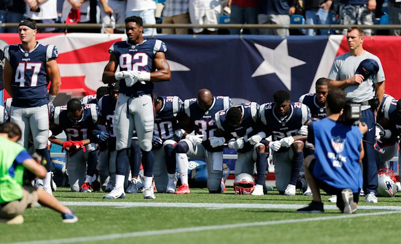 Members of the New England Patriots take a knee during the national anthem before a game against the Houston Texans at Gillette Stadium.