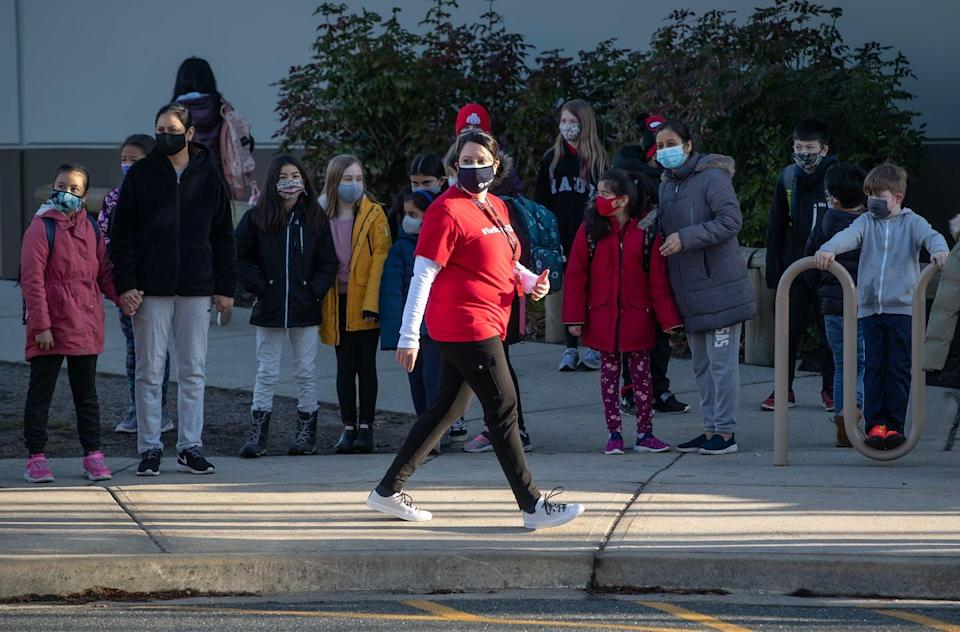 """<span class=""""caption"""">Students watch as a teacher participates in a solidarity march with colleagues to raise awareness about COVID-19 cases at École Woodward Hill Elementary School, in Surrey, B.C., Feb. 23, 2021. </span> <span class=""""attribution""""><span class=""""source"""">THE CANADIAN PRESS/Darryl Dyck</span></span>"""