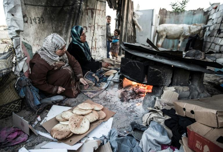 Palestinian women bake bread next to their makeshift home in the Khan Yunis refugee camp in the southern Gaza Strip on April 19, 2017
