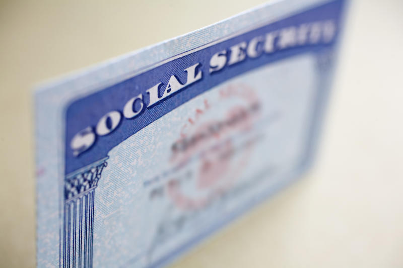 A Social Security card standing up on a table, with the name and number blurred out.