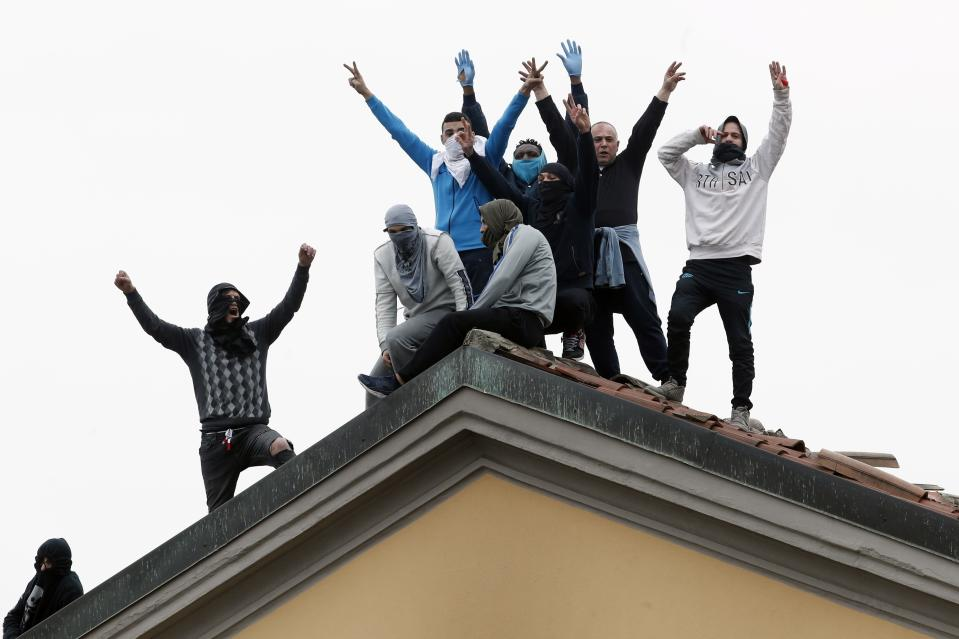 Multiple inmates on the roof of the San Vittore prison in Milan raising their arms in protest.