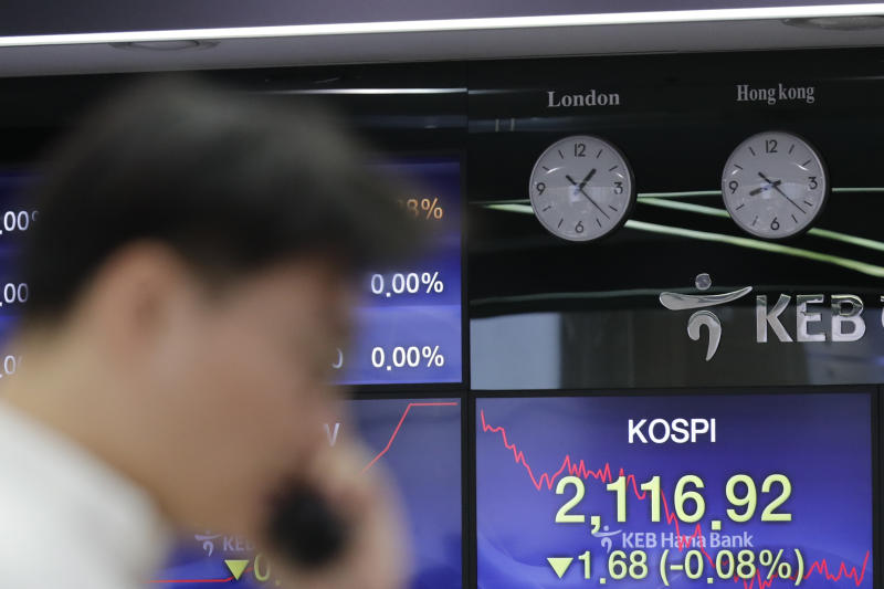 A currency trader talks on the phone near the screen showing the Korea Composite Stock Price Index (KOSPI) at the foreign exchange dealing room in Seoul, South Korea, Friday, Nov. 29, 2019. Shares extended losses in Asia on Friday after Japan and South Korea reported weak manufacturing data that suggest a worsening toll from trade tensions. (AP Photo/Lee Jin-man)