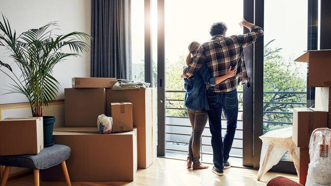 relaxed middle aged couple holding each other while looking out on their balcony together at their new home.