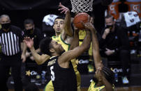 Colorado guard D'Shawn Schwartz (5) and Oregon guards Chris Duarte (5) and LJ Figueroa (12) vie for a rebound during the first half of an NCAA college basketball game Thursday, Feb. 18, 2021, in Eugene, Ore. (AP Photo/Andy Nelson)