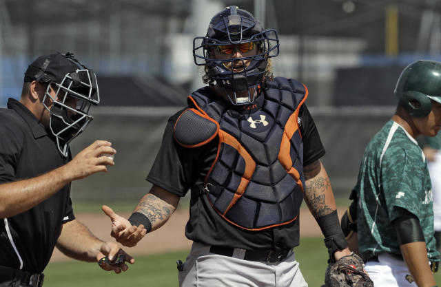 Major League Baseball free agent catcher Jarrod Saltalamacchia, center, gets a new baseball during a scrimmage, Tuesday, Feb. 27, 2018, in Bradenton, Fla. (AP Photo/Chris O'Meara)
