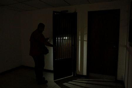 A worker uses light from a phone while he opens a door at the Padre Justo hospital, during a blackout in Rubio, Venezuela March 14, 2018. Picture taken March 14, 2018. REUTERS/Carlos Eduardo Ramirez