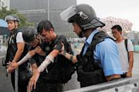 A protester who was pepper sprayed is detained during the anniversary of Hong Kong's handover to China in Hong Kong