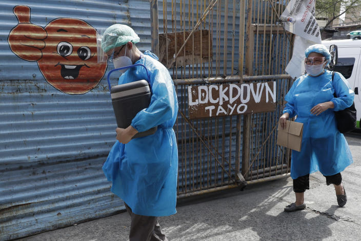 Doctor Kenneth Maturgo carries China's Sinovac COVID-19 vaccines as they prepare to inoculate residents who are not able to go to vaccination centers in Manila, Philippines on Wednesday, May 19, 2021. Philippine President Rodrigo Duterte has eased a lockdown in the bustling capital and adjacent provinces to fight economic recession and hunger but has still barred public gatherings this month, when many Roman Catholic festivals are held. (AP Photo/Aaron Favila)