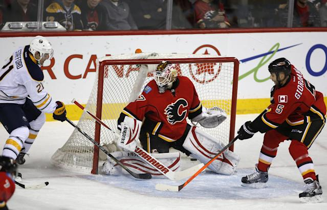 Buffalo Sabres' Drew Stafford (14) scores past Calgary Flames goalie Joni Ortio, of Finland, as Flames' Mark Giordano (5) defends during first period NHL hockey action in Calgary, Alberta, on Tuesday March 18, 2014. (AP Photo/The Canadian Press, Jeff McIntosh)