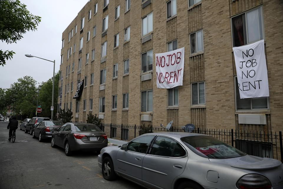 Makeshift sheets displaying messages of protest contesting the ability to pay for rent hang in the window of an apartment building in the Columbia Heights neighborhood in Washington, U.S., May 18, 2020. REUTERS/Tom Brenner