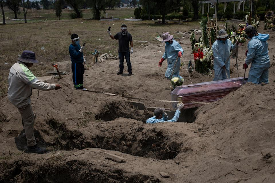 Two family members film the makeshift funeral in Mexico City. Source: Getty