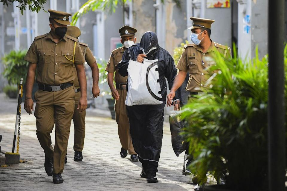Former Maldivian state minister for Finance and Treasury Mohamed Ashmalee (centre) is escorted out of the Colombo Fort Magistrates court. Source: Getty